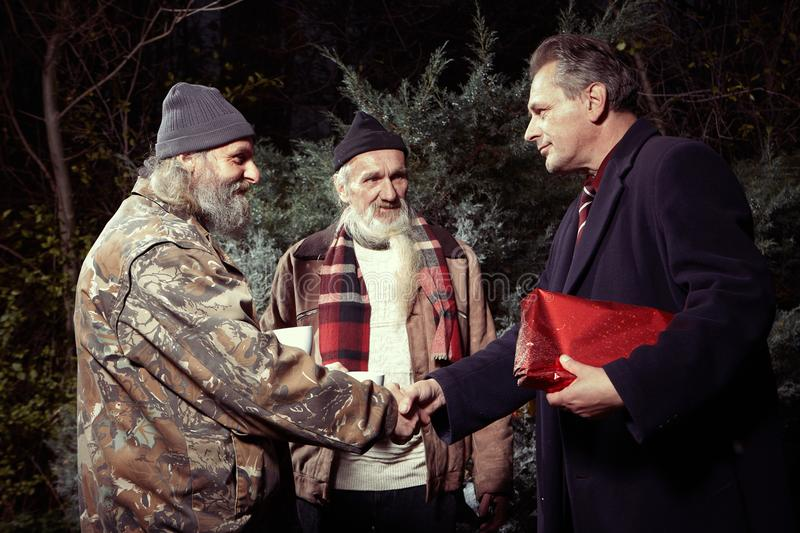 Rich man getting gift for his help to poor homeless. Two homeless older men rewarding manager men for gift of food royalty free stock images