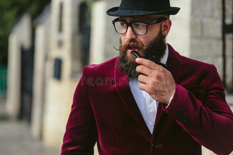 Rich man in a jacket near his house. A rich man with a beard smokes electronic cigarette royalty free stock image
