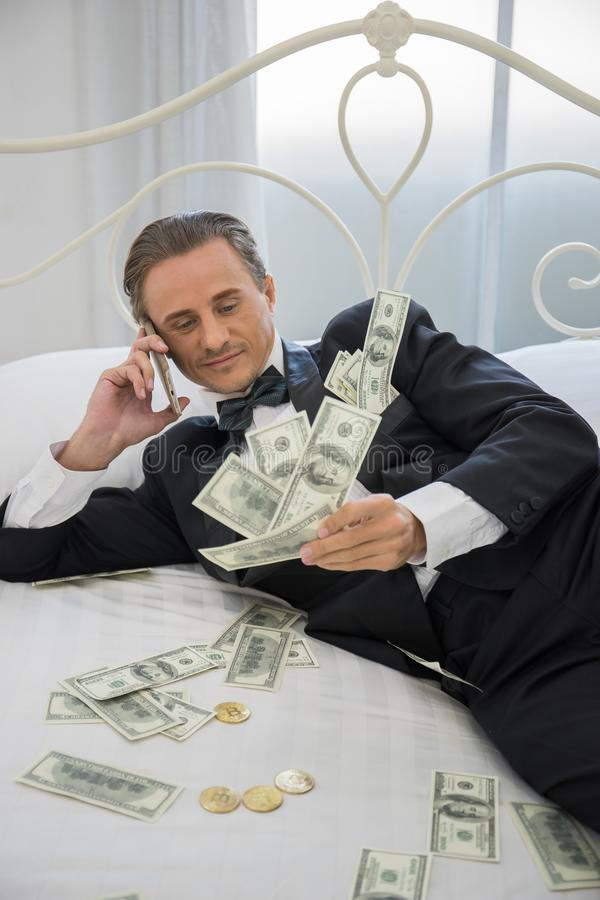 Rich man lying on the bed with dollar banknotes. Success business stock photo