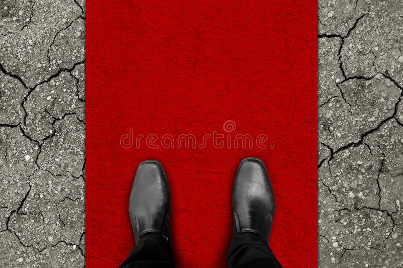 Rich man on red carpet and poor world. Rich man standing on red carpet but poor world waiting for helping and sharing around him royalty free stock photo