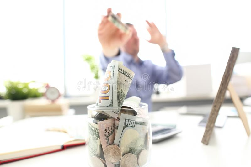 Rich man throwing US banknotes in big jar full of money at workplace. Closeup stock photos