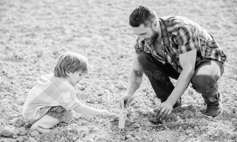 Rich natural soil. Eco farm. new life. soils and fertilizers. small boy child help father in farming. father and son. Planting flowers in ground. happy earth stock photography