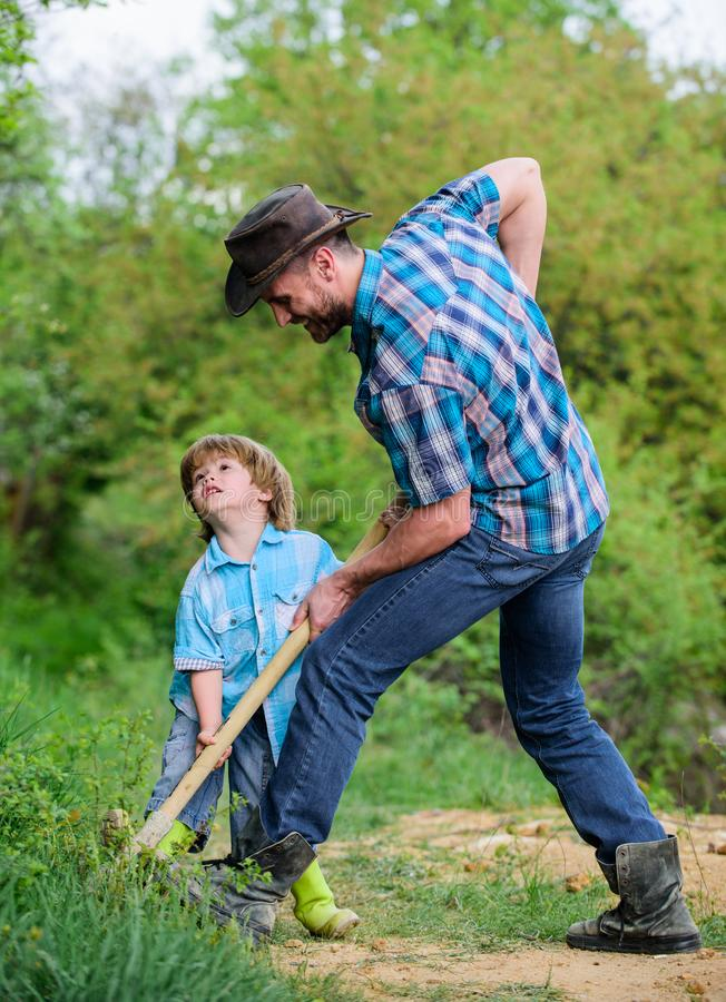 Rich natural soil. Eco farm. Ranch. new life. soils and fertilizers. small boy child help father in farming. father and. Son planting family tree. earth day stock photo