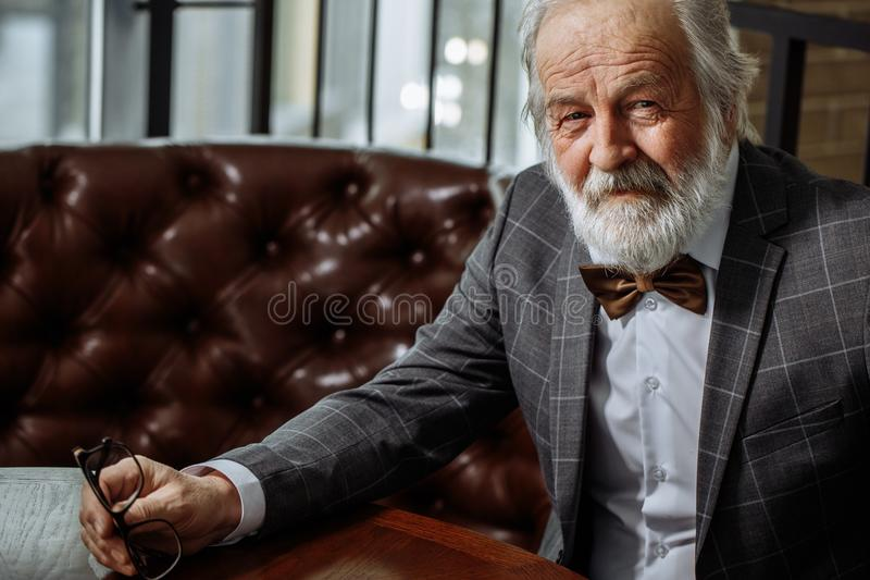 Rich old pleasant man is looking at camera. closeup cropped photo royalty free stock images