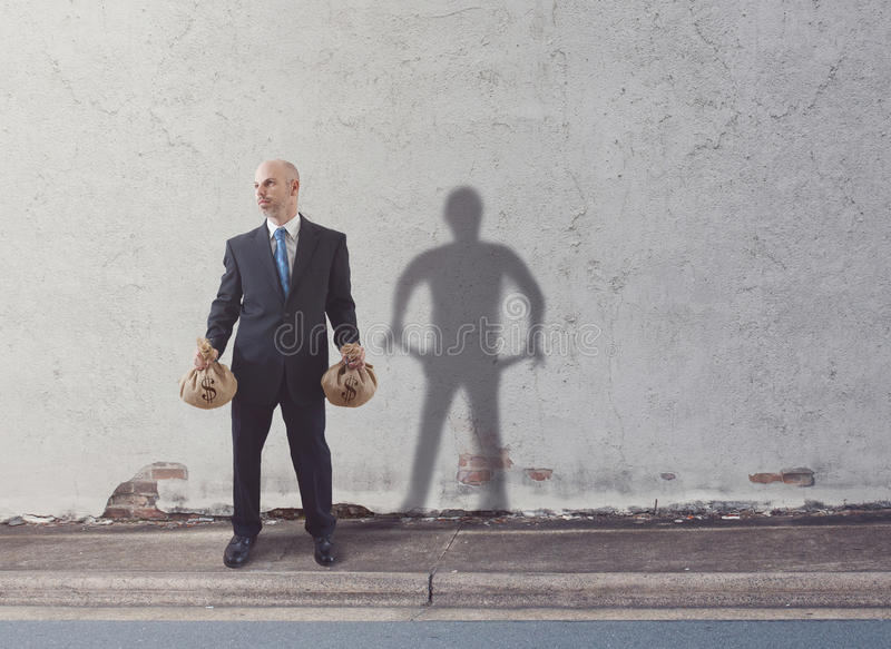 Rich and poor. A rich man with a lot of money casts a shadow of being poor stock images