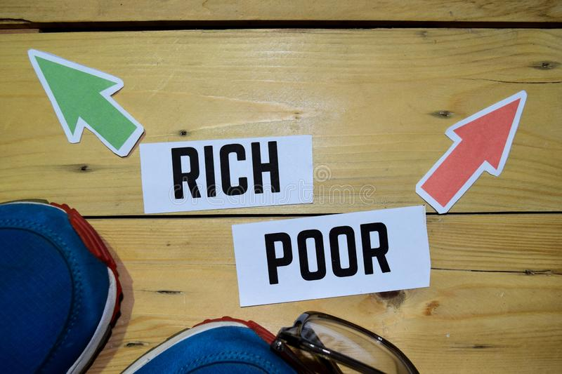 Rich or Poor opposite direction signs with sneakers and compass on wooden vintage background. Business and education concepts royalty free stock image