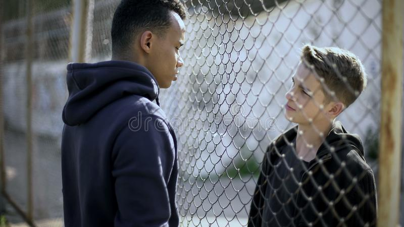 Rich and poor separated by fence, two boys of different nationalities talking. Stock photo royalty free stock photo