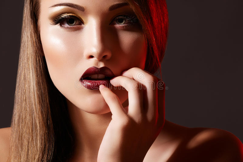 Rich retro diva. Fashion model with evening makeup. Chic evening style. Glamour portrait of alluring woman model. She's wearing luxury fashion make-up, dark red stock photography