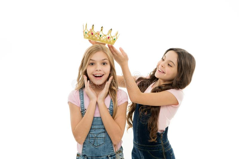 Rich reward. Little girl putting crown on head of small beauty queen winner as reward. Adorable mini miss beauty pageant royalty free stock images