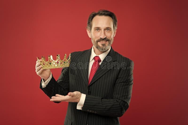 Rich reward. Mature businessman showing crown reward on red background. Successfil big boss awarding winner with royalty free stock image