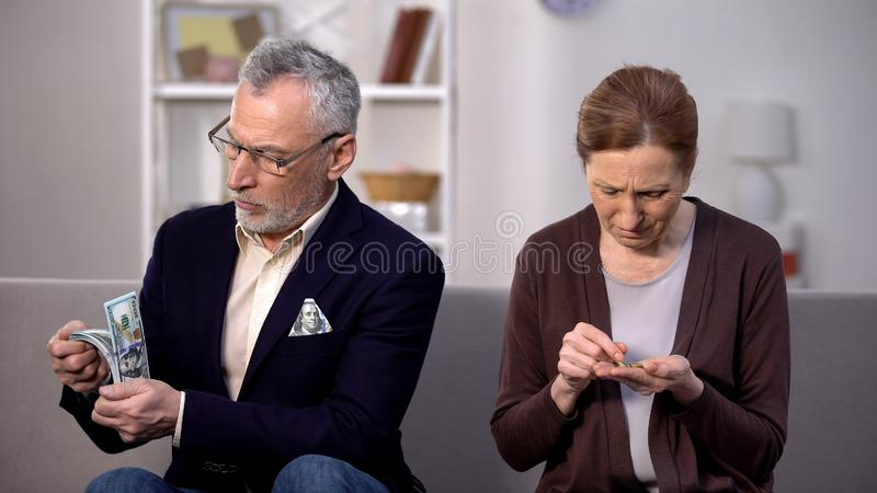 Rich senior man holding dollars, poor woman counting coins, social gap, money. Stock photo royalty free stock photography