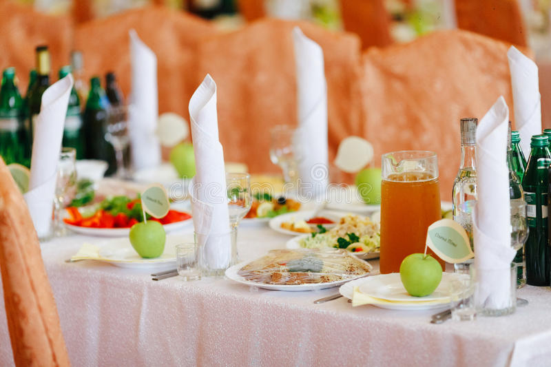 Rich table served for a dinner and green apples on an empty plat royalty free stock images
