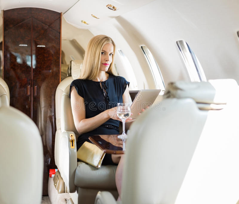 Luxury Woman On Airplane : Rich woman using tablet computer in private jet royalty