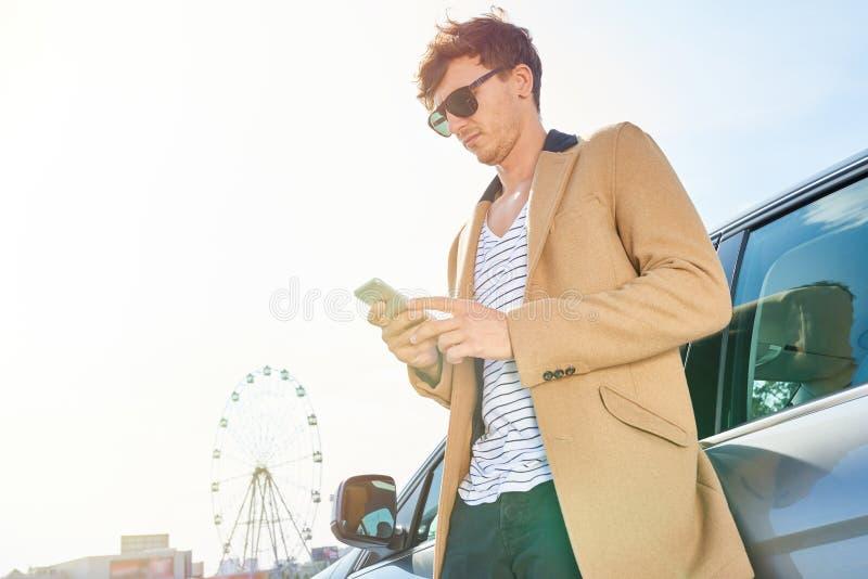 Rich Young Man Leaning en el coche al aire libre imagen de archivo