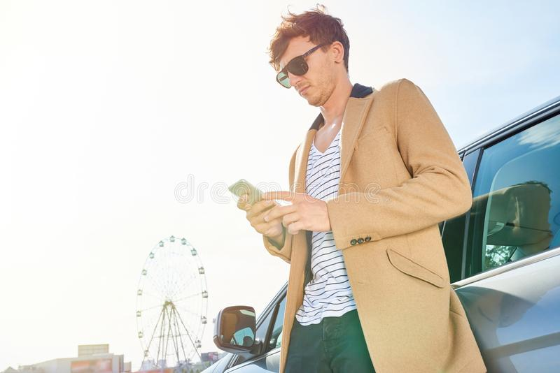 Rich Young Man Leaning sull'automobile all'aperto immagine stock