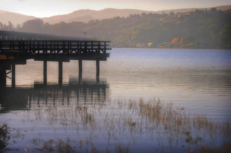 Richardson Bay, Marin County, California. The rising sun paints its golden early morning light through the fog over the landscape, and a pier juts out into the royalty free stock image