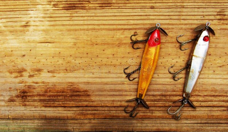 Richiami d'annata di pesca parallelamente su fondo di legno immagini stock libere da diritti