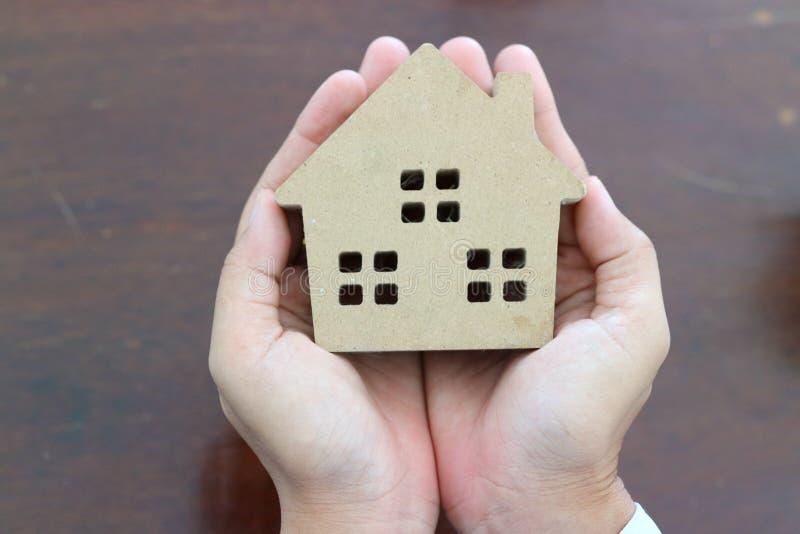 Richiesta di una casa di legno in un woman& x27; mano di s Concetto di soldi di risparmio per comprare una casa immagine stock
