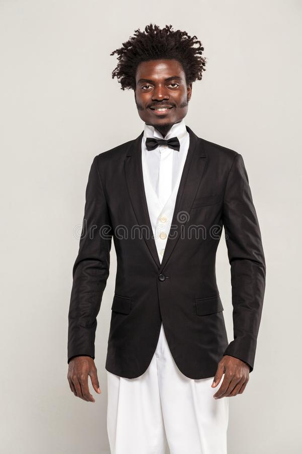 Richly african gentelman in tuxedo and bow of tie smiling royalty free stock images
