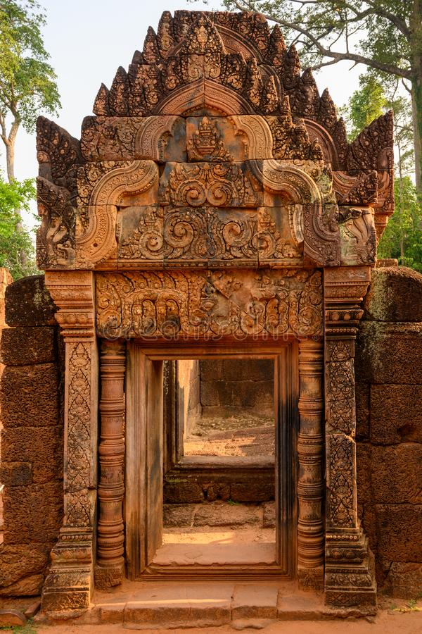 Richly decorated entrance door of Temple Banteay Srei, Cambodia. Carvings from Hindu mythology on walls Banteay Srei, Angkor Wat. Richly decorated entrance door royalty free stock photography
