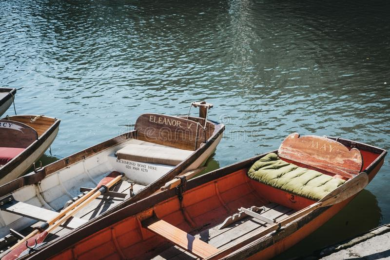 Richmond Bridge Boat Hire wooden boats moored on the River Thames in Richmond, London, UK. London, UK - August 1, 2018. Richmond Bridge Boat Hire wooden boats royalty free stock image