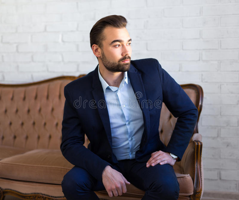 Richness and success concept - handsome man in business suit sit royalty free stock photo