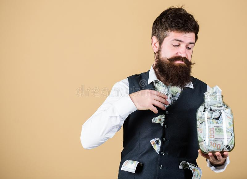 Richness and wellbeing. Security and money savings. Banking concept. Man bearded guy hold jar full of cash savings. Safe. Place to keep money. Personal stock image
