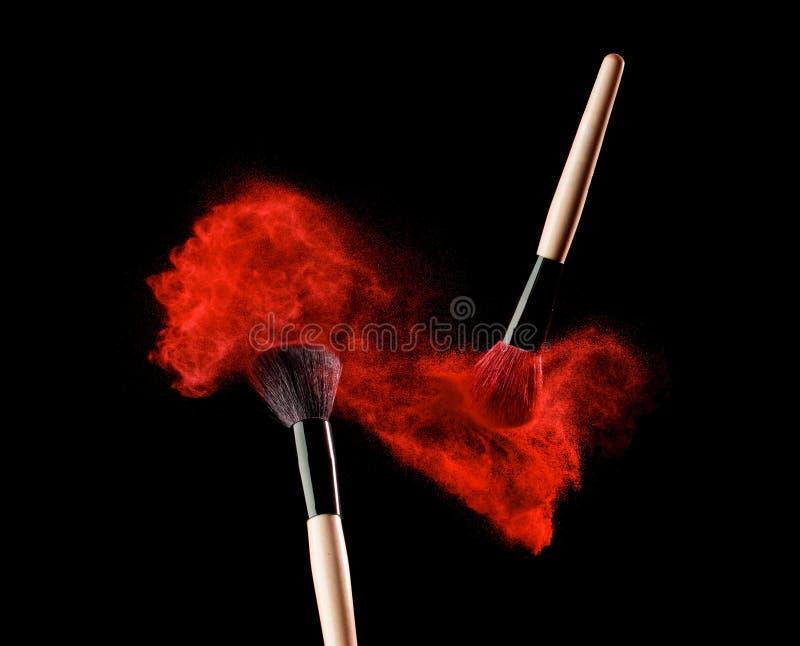 Richten Sie Bürste mit Pulverexplosion auf schwarzem Hintergrund her stockfoto