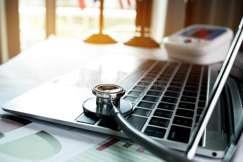 Richten Sie Stethoskop-Doktortabelle auf Laptop-Computer mit dem Bericht stockbilder