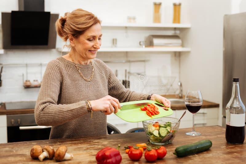 Richtend hethaired vrouw blijven in keuken en het voorbereiden van lichte maaltijd royalty-vrije stock foto's