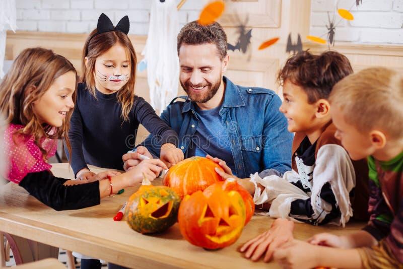Richtende mens die zijn kinderen en neven voor Halloween-partij uitnodigen royalty-vrije stock fotografie