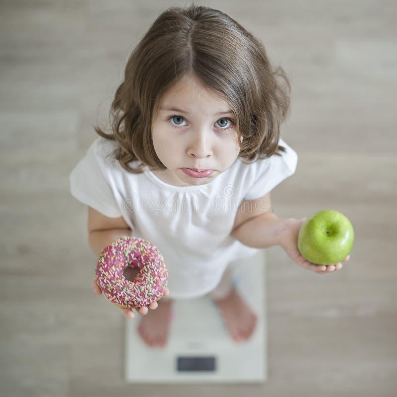 Richtige Auswahl Wenig trauriges Mädchen, das im Handgrünem Apfel und in highcalorie Donut hält Kind, das versucht, Entscheidung  lizenzfreie stockbilder