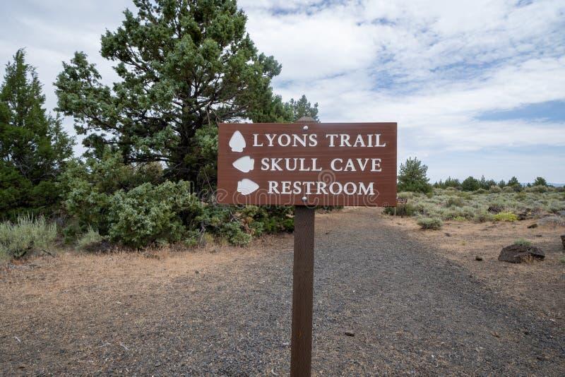Richtingaanwijzer in Lava Beds National Monument leidt wandelaars naar toiletten, grotten en het Lyons-spoor stock afbeelding