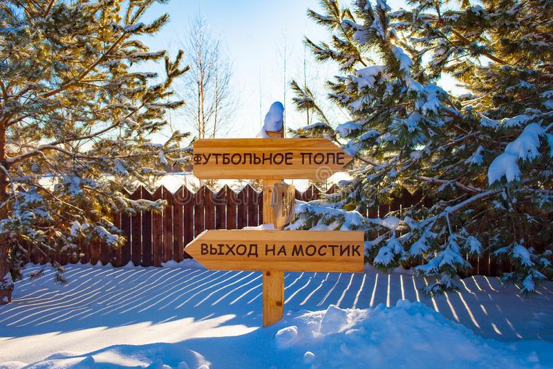 Richtingsindicator van hout wordt gemaakt dat Het landschap van de winter Sneeuw en Spruce De inschrijving op het teken in Rus royalty-vrije stock afbeelding