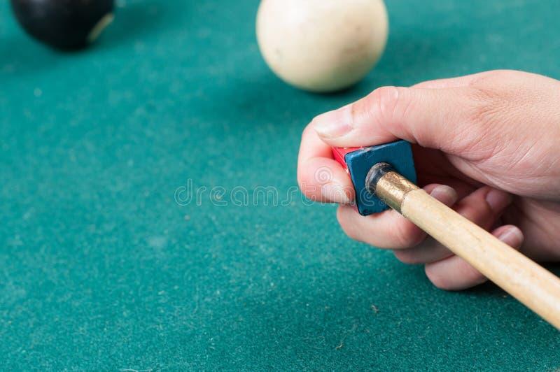 Richtsnoerstok met krijtblok op groene biljartlijst Krijtblok op poollijst stock afbeelding
