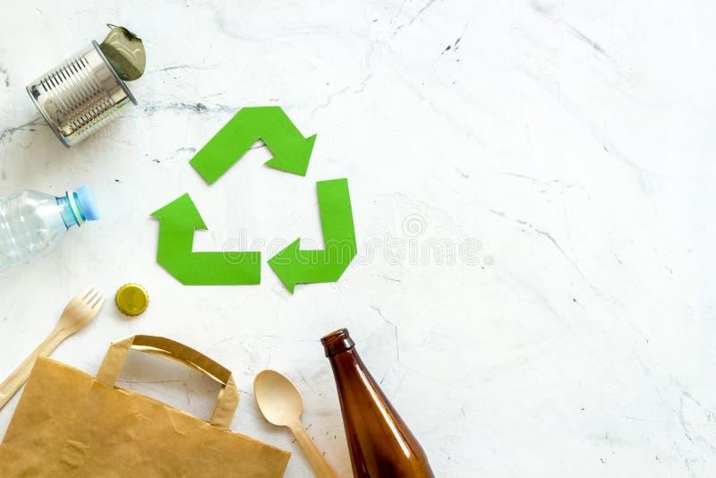 Riciclando segno con i materiali riciclati, sacco di carta, bottiglia, latta per il concetto di ecologia su derisione di marmo di fotografia stock libera da diritti