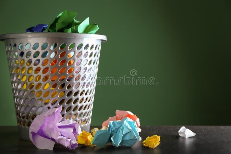 Ricicli il recipiente con le carte sgualcite sulla tavola contro il fondo di colore fotografia stock