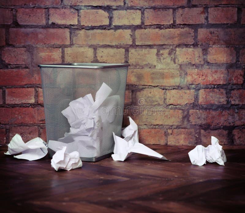Ricicli il recipiente riempito di carte sgualcite. Fondo del muro di mattoni fotografia stock