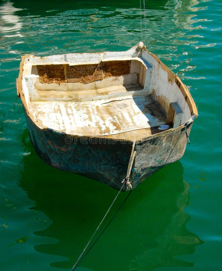 Old Row Boat. Fisherman`s derelict row boat is still afloat in the harbor emerald waters of Huatulco, Mexico royalty free stock photos