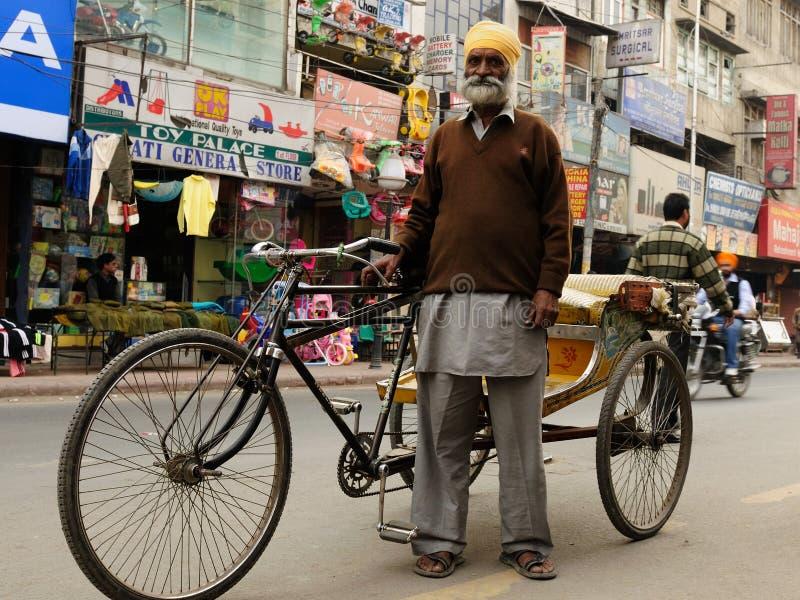 Rickshaw driver, India. INDIA, AMRITSAR - NOVEMBER 29: Rickshaw driver with one's rickshaw in the street of Indian city, Amritsar in November 29, 2009 royalty free stock photo