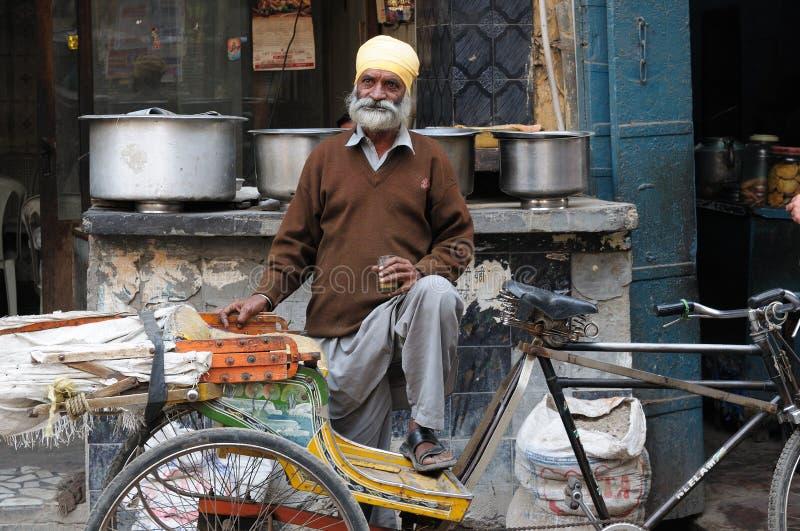 Rickshaw driver, India. INDIA, AMRITSAR - NOVEMBER 29: Rickshaw driver with one`s rickshaw in the street of Indian city royalty free stock photo