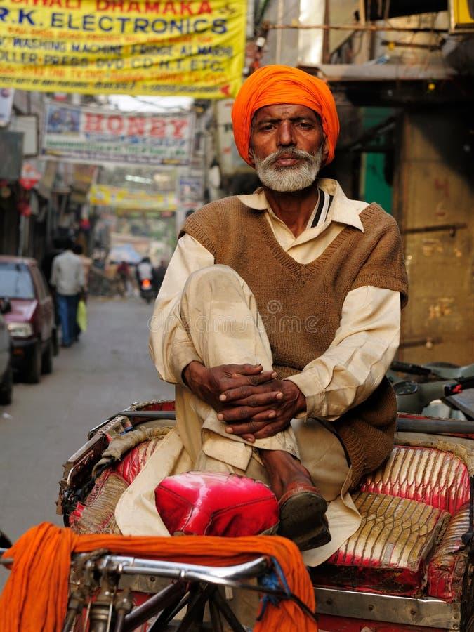 Rickshaw driver, India. INDIA, AMRITSAR - NOVEMBER 29: Rickshaw driver with one's rickshaw in the street of Indian city, Amritsar in November 29, 2009 royalty free stock photography