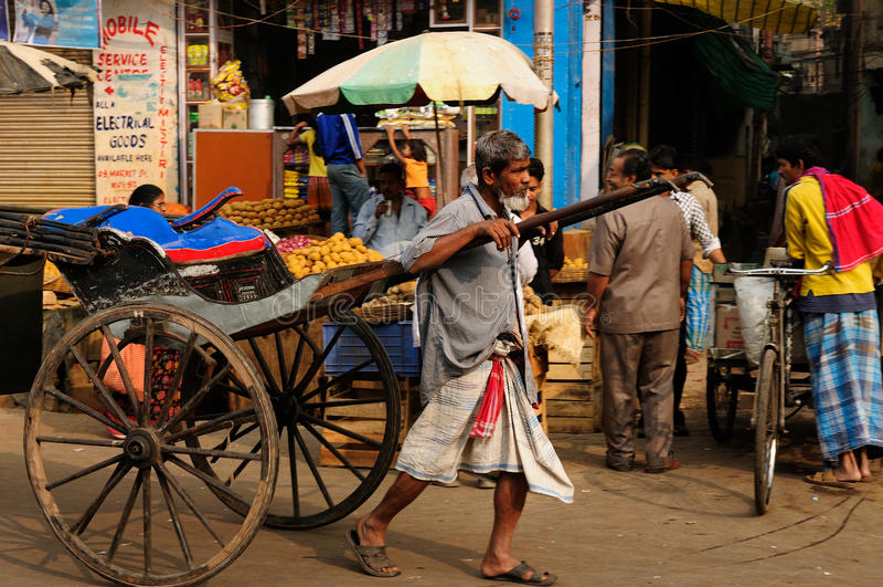 Rickshaw driver, India. KOLKATA, INDIA - DECEMBER 14: Rickshaw driver with one's rickshaw in the street of Indian city, Kolkata in December 14, 2009 royalty free stock images
