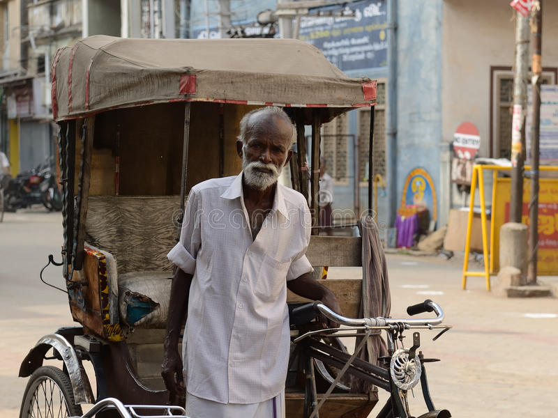 Rickshaw driver, India. INDIA, MADURAJ - MARCH 05: Rickshaw driver with one's rickshaw in the street of Indian city, Maduraj in March 05, 2015 stock photography