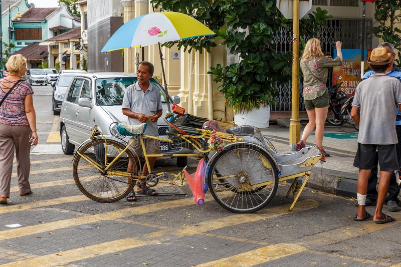 Rickshaw driver waiting for customer on Georgetown Street. George Town, Penang, Malaysia - November 26, 2017: Rickshaw driver waiting for customer on Georgetown royalty free stock image
