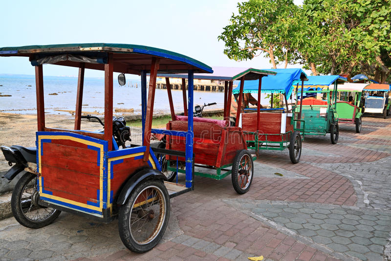 Rickshaw in Indonesia. Row of rickshaws on the background of sea, Bintan, Indonesia royalty free stock photos