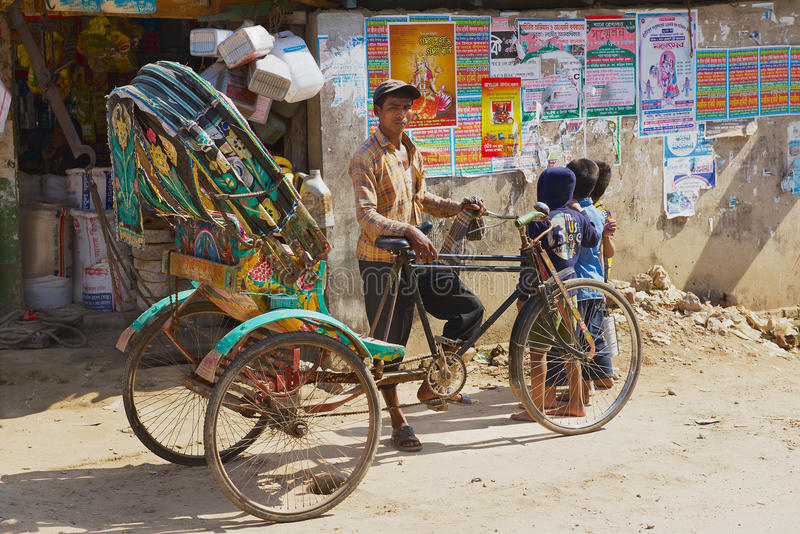 Rickshaw waits for passengers at the street in Bandarban, Bangladesh. BANDARBAN, BANGLADESH - FEBRUARY 20, 2014: Unidentified rickshaw waits for passengers at stock photos