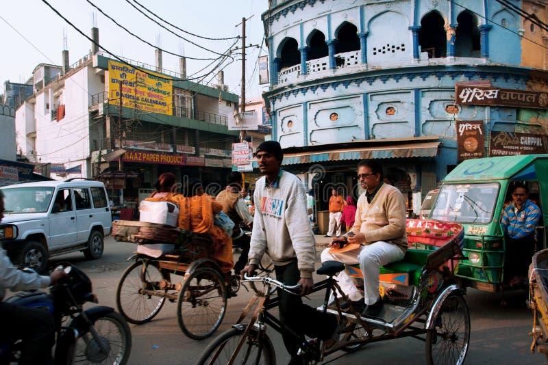 Rickshawen kör till och med den fullsatta gatan med många cyklar i Lucknow, Indien arkivfoton