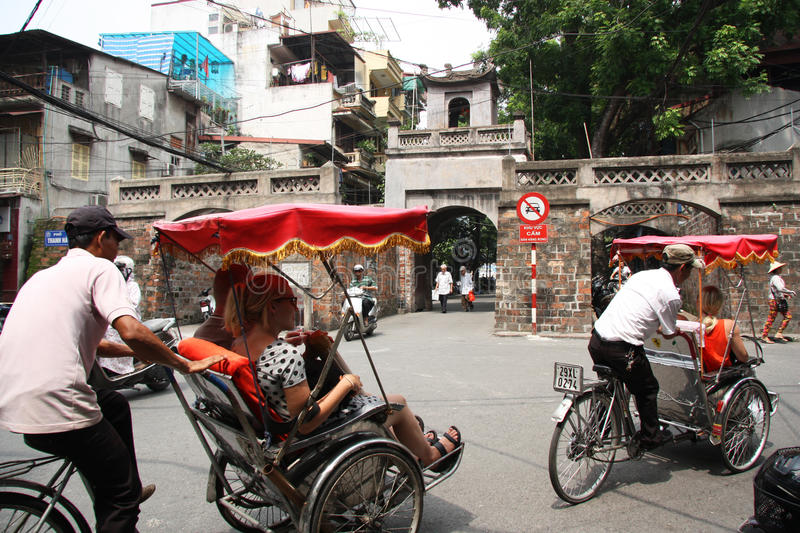 Rickshaws drive tourists in a street of Hanoi stock images