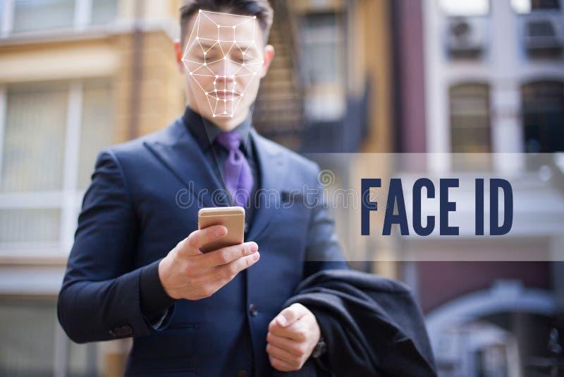 Riconoscimento del volto e sblocco di uno smartphone per strada Un uomo con una tuta da lavoro che guarda il telefono ID faccia fotografia stock libera da diritti